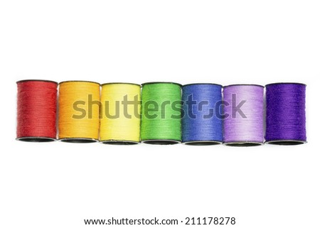 rainbow colored spools of cotton thread on white - stock photo