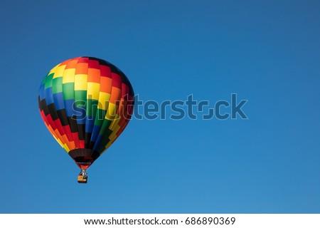 Rainbow colored tear drop shaped hot air balloon against cloudless blue sky