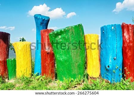 Rainbow-colored wood decoration in garden. Shot near Tyudiv, Carpathian Mountains, Ukraine.  - stock photo