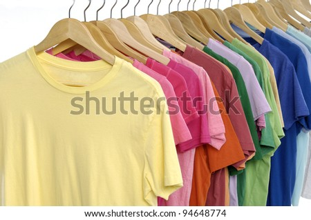 Rainbow colors. Choice of casual clothes on wooden hangers - stock photo
