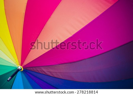 Rainbow coloured umbrella - stock photo