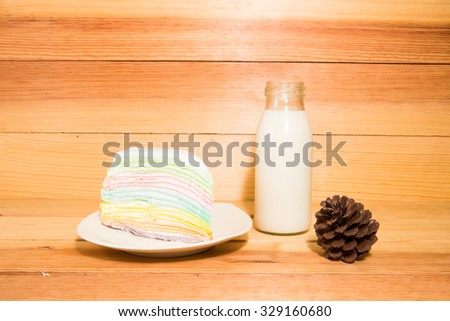 Rainbow crape cake with milk on plate on wooden table