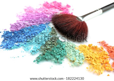 Rainbow crushed eyeshadow and professional make-up brush close up - stock photo
