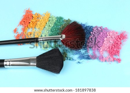 Rainbow crushed eyeshadow and professional make-up brush on blue background