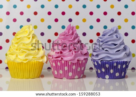 Rainbow cupcakes on a dotted background