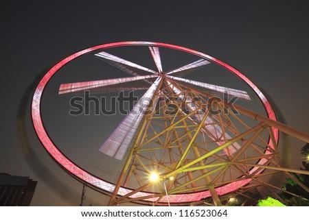 Rainbow ferris wheel at night - stock photo