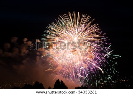 Rainbow fireworks over a bay - stock photo