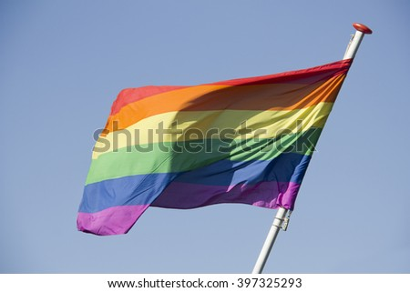 Rainbow Flag against a blue sky on Coming Out Day for homosexuals