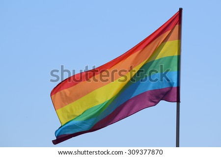rainbow flag against the blue sky, symbol of tolerance and acceptance, diversity, hope and longing. The colors of this flag are specially for LGBT (Lesbian, Gay, Bisexual, Transgender) Pride. - stock photo
