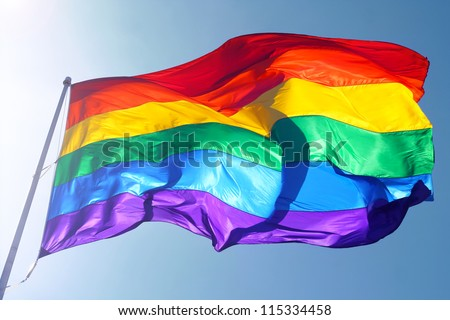 Rainbow flag, sun, wind, and blue sky