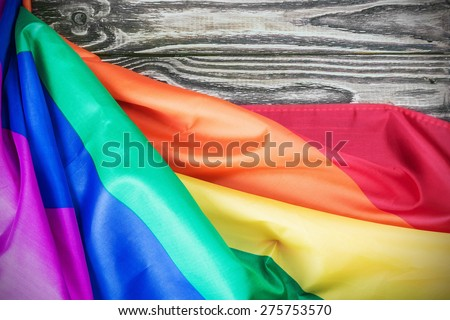 Rainbow gay flag on a wooden table. Focus on flag - stock photo