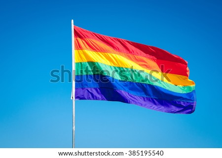 Rainbow Gay Pride Flag on blue sky background - stock photo