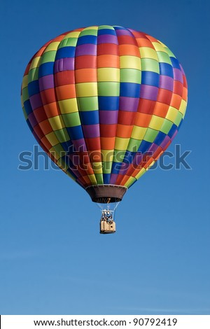 Rainbow Hot Air Balloon in Flight - stock photo