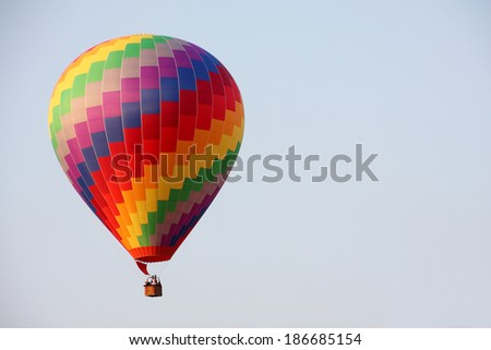 Rainbow hot air balloon on blue sky - stock photo