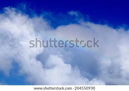 Rainbow in blue cloudy sky. - stock photo