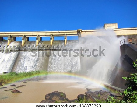 Rainbow in front of a dam wall. Shot in Hazelmere Dam Nature Reserve, near Durban, North Coast of Kwazulu-Natal, South Africa. - stock photo