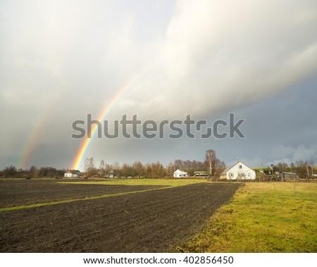 rainbow in sky after autumn rain - stock photo