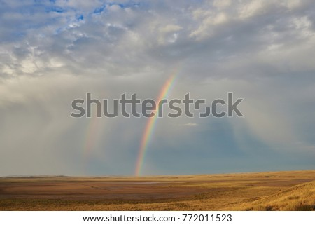 Rainbow in sky among  landscape over the boundless savannah, summer nature background, blue sky with clouds for summer adventure. The rainbow crosses the sky over desert. The concept of exotic tourism