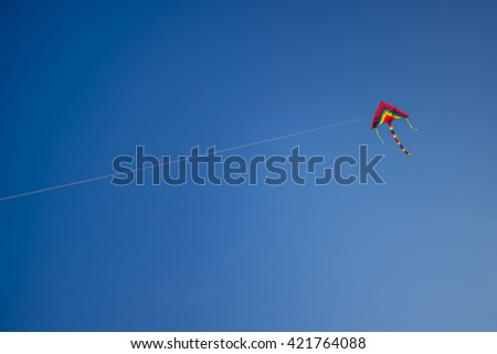 Rainbow kite on a background of blue sky. Space for text