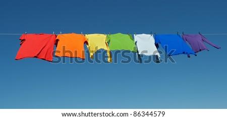 Rainbow laundry. Bright shirts on a clothesline on a blue sky background. - stock photo