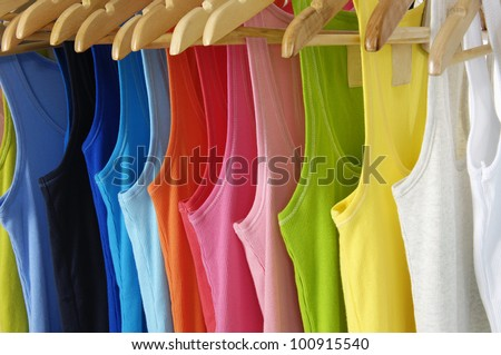 rainbow many peignoir hanging on wooden hangers-background - stock photo