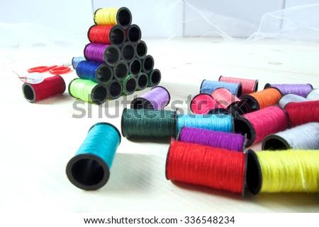 Rainbow of colourful thread spools on the table - stock photo