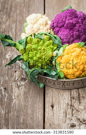 Rainbow of organic cauliflower and Romanesco broccoli on wooden table. Also available in horizontal format.