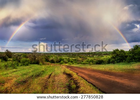Rainbow on a background of the spring landscape - stock photo
