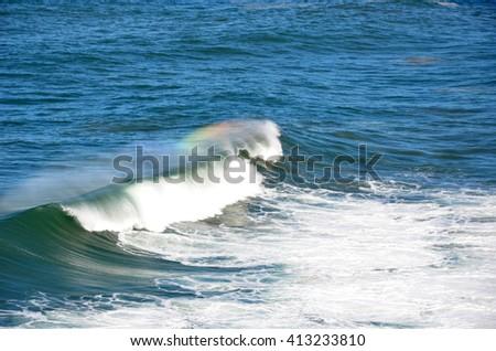 Rainbow on wave spray in the ocean - stock photo