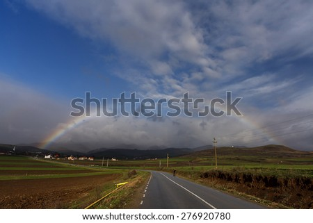Rainbow over a road to the village and farmland - stock photo