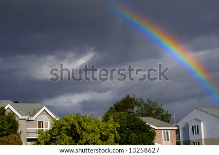 Rainbow over a typical American town after a thunderstorm - stock photo