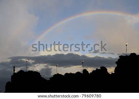 """Rainbow over """"Black Rock"""" in Maui, Hawaii. Torches and one person on the high cliff with arms opened. Silhouette at dusk. - stock photo"""