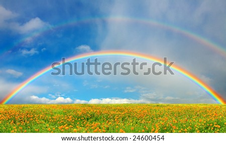 Rainbow over field - stock photo