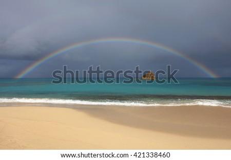 Rainbow over Hawksbill Rock, Hawksbill, Antigua - stock photo
