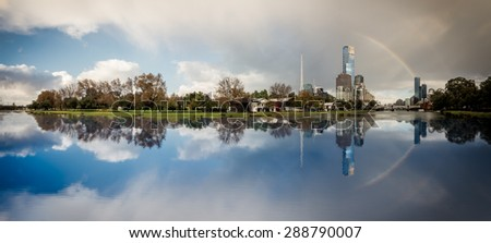 rainbow over melbourne city reflected in the yarra river on a winter day