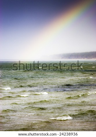 Rainbow over overcasting sea scene - stock photo