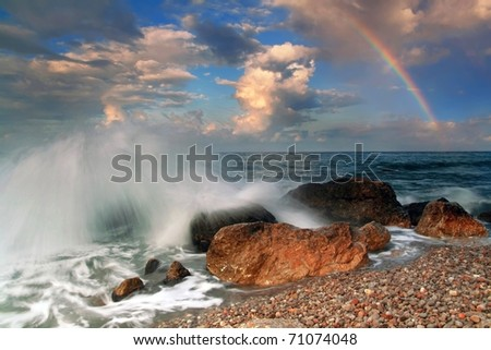 Rainbow over stormy sea in the early morning - stock photo