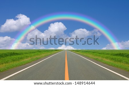 Rainbow over straight road - stock photo