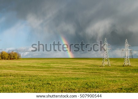 Rainbow over the field and high voltage poles