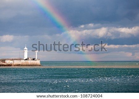 rainbow over the sea and a beacon