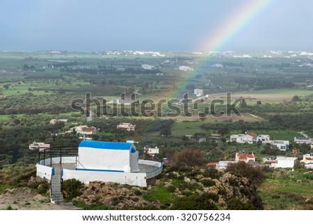 Rainbow over traditional church after rain in Kos Island, Greece - stock photo
