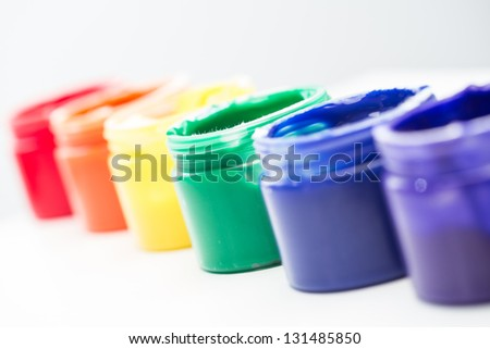 Rainbow paint pots in a line for gay pride on white background - stock photo