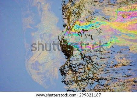 rainbow reflection of crude oil spill on the stone at the beach
