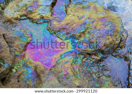 rainbow reflection of crude oil spill on the stone at the beach - stock photo