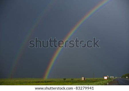 Rainbow's end. Beautiful view on rainy and sunny landscape. - stock photo