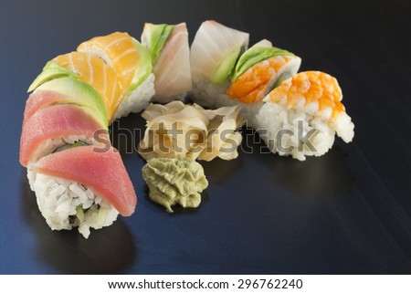 Rainbow sushi roll sliced with wasabi and fresh ginger - stock photo