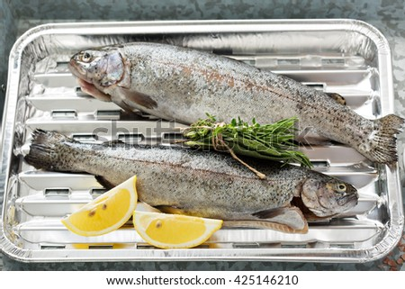 Rainbow trout on a foil dish ready to be grilled - stock photo