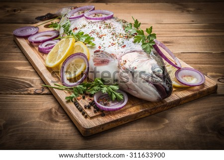 Rainbow trout with fresh spices on the wooden - stock photo