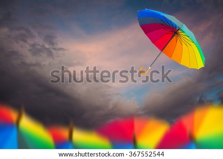 Rainbow umbrella floating over dark clouds abstract background