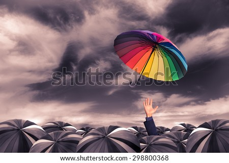 rainbow umbrella fly out from the business man hand amoung the mass of black umbrellas - stock photo